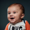 Baby boy smiling to the left on dark grey background