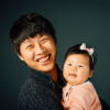 Father and baby daughter smiling in Studio session