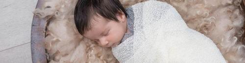 Baby in white wrap sleeping on woollen fleece in Sydney studio session
