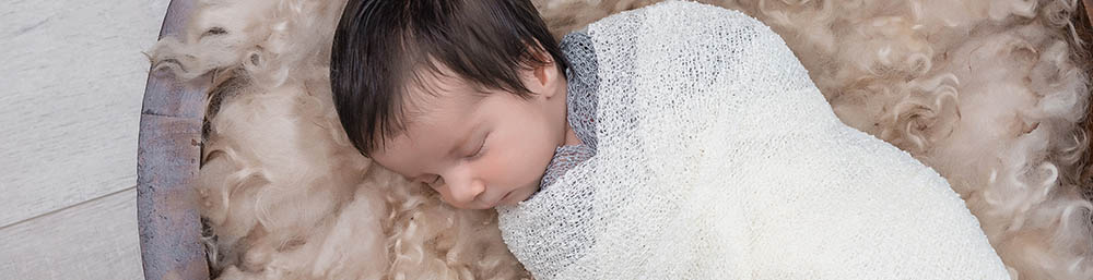 Baby in white wrap sleeping on woollen fleece in Sydney studio session
