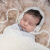 Baby in white wrap and bonnet sleeping on woollen fleece