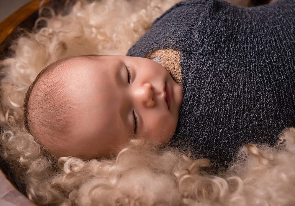 Wrapped newborn baby boy sleeping in bucket in Sydney photography session