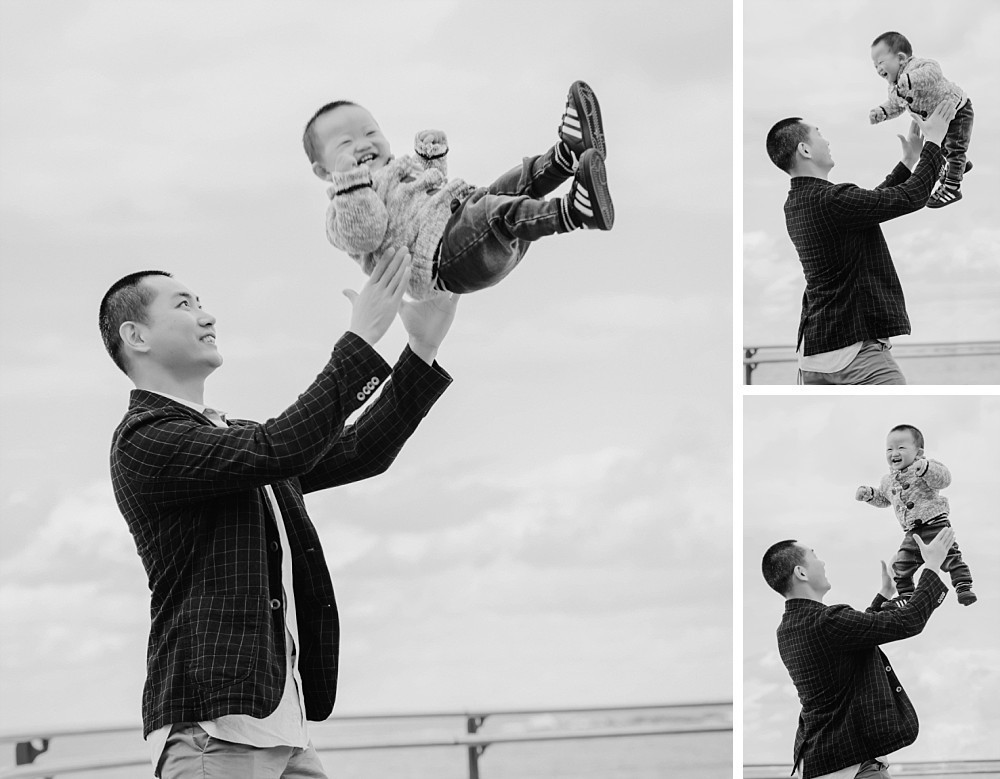 Father throwing 1 year old boy in the air at Coogee Beach Sydney