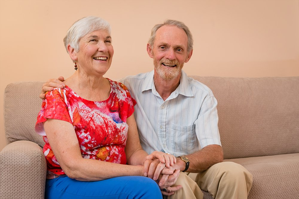 Older Caucasian couple sitting on sofa holding hands smiling in Sydney