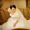 Asian in wedding dress walking up stairs