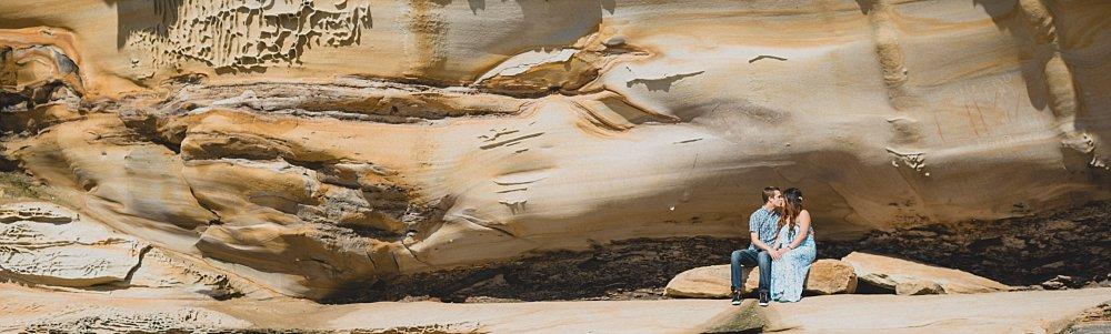 Pregnant couple sitting against sandstone cliff La Perouse
