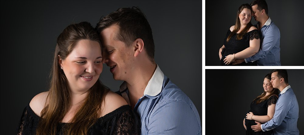 Caucasian maternity couple in Sydney studio in embrace on dark background