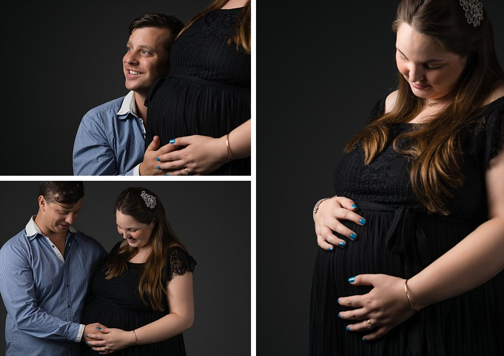 Caucasian maternity couple in Sydney studio in embrace on dark background and light from side