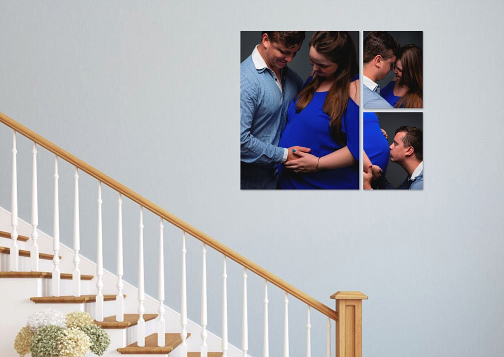 Wall art of Caucasian maternity couple above staircase