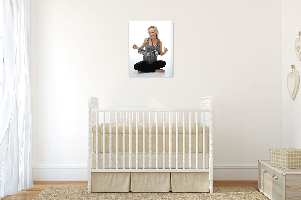 Artwork of blonde pregnant woman sitting cross legged looking at ultrasounds