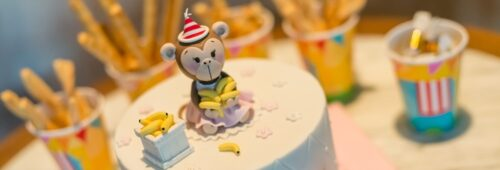 Birthday cake with monkey figure and party cups