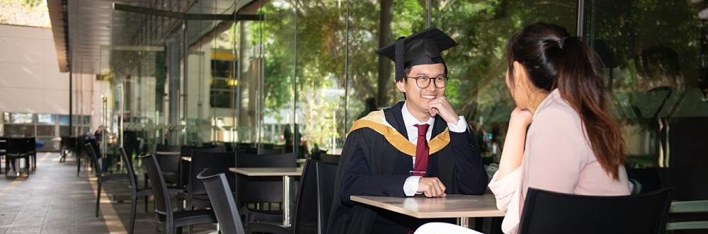 Young Asian couple at UNSW Tyree building in graduation gown