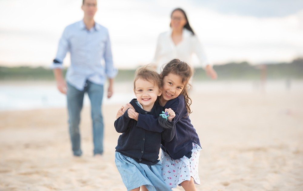 Two young mixed girls hugging on beach with parents blurred in background
