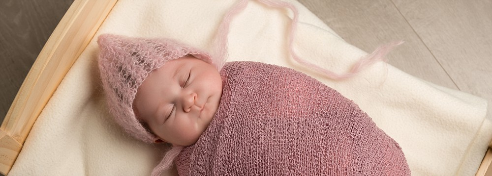 Newborn baby girl in pink wrap and bonnet in bed