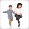 3 year old boy and 5 year old girl dancing in studio high key