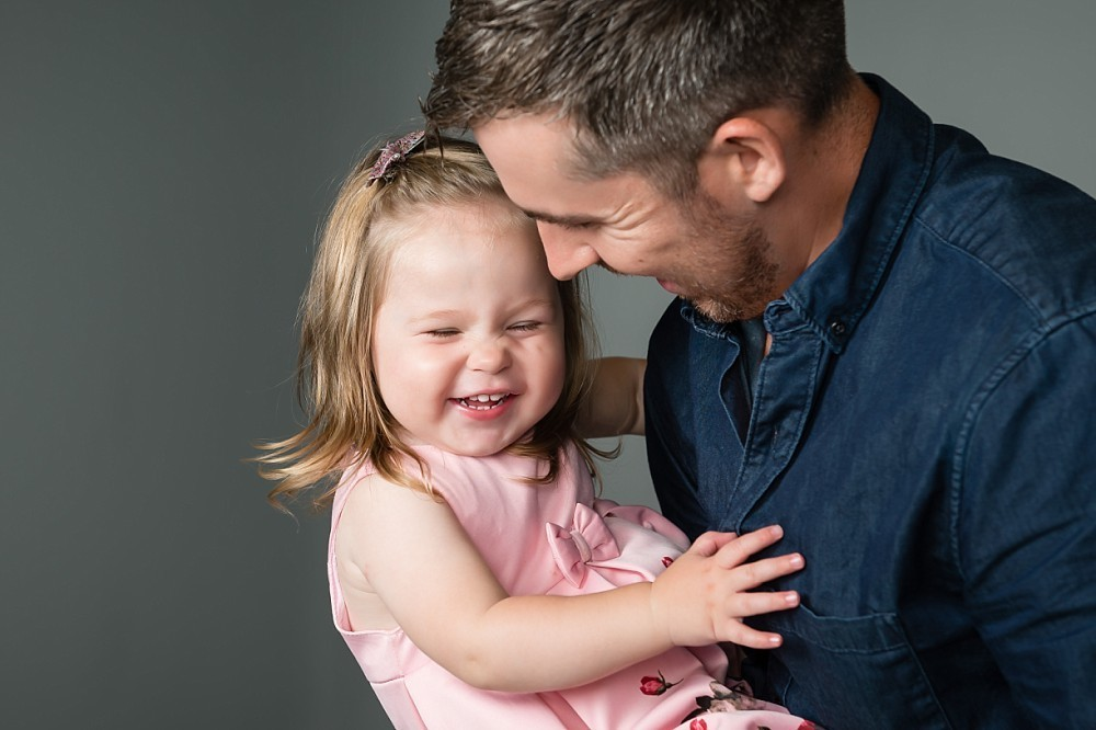 Father holds laughing 2yr old daughter in Sydney studio