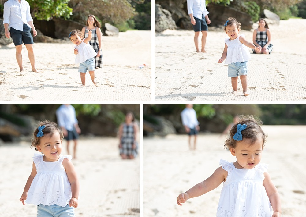 2 year old girl on Sydney beach walking with mum and dad in background