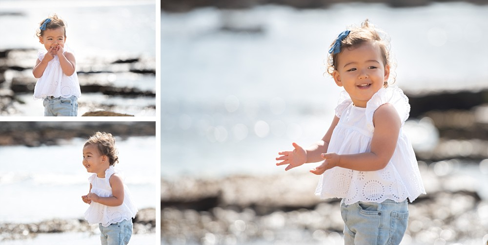 2 year old girl on beach with rocks and sea in background in Sydney