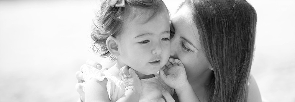 Mum kissing 2 year old daughter