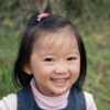3 year old Asian girl at Lane Cove Park smiling at camera