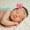 Newborn baby girl sleeping with pink head decoration