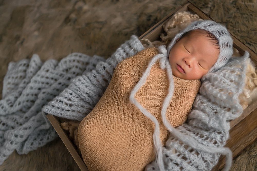 Newborn baby boy in wrap and bonnet in Sydney Studio session