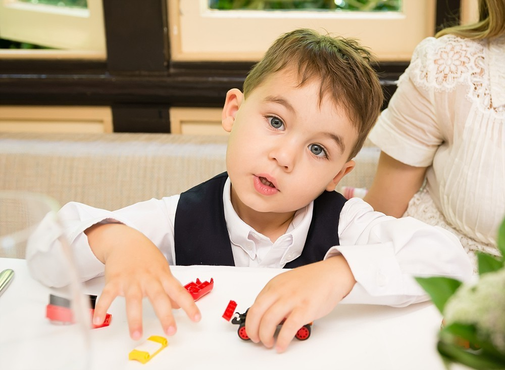 Young boy at table tilts head with cute expression