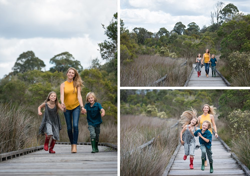 Mum, a boy and girl running on a wooden deck amongst tall grasses
