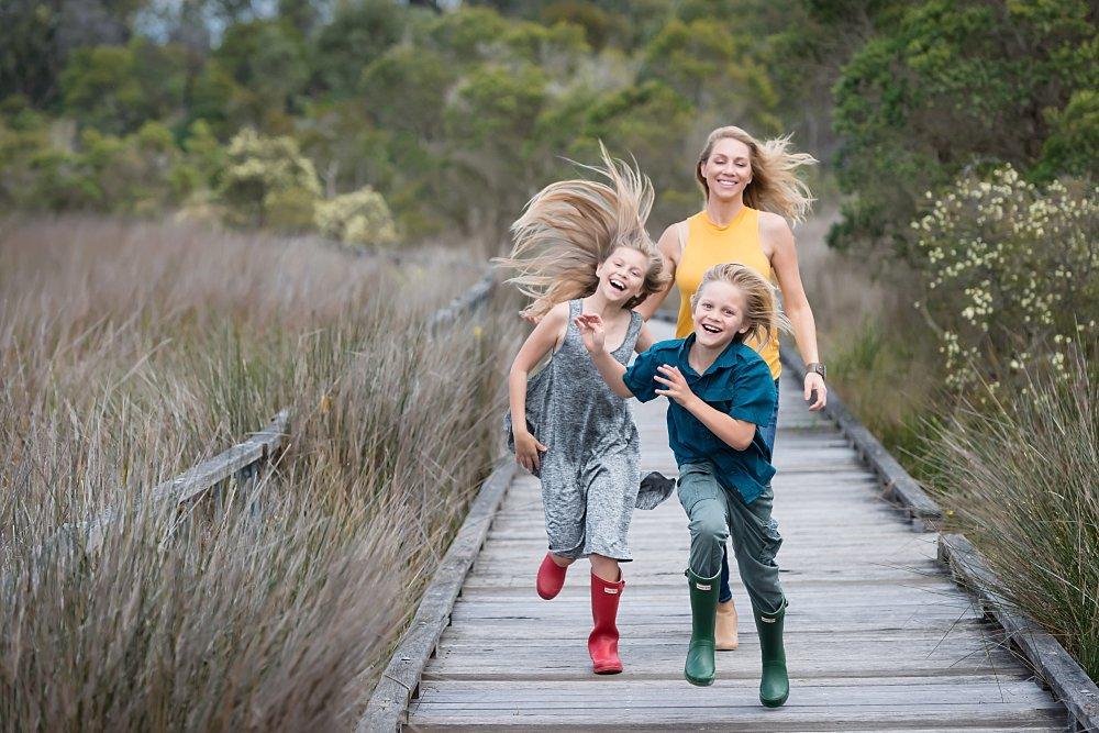 Mum, a boy and girl running on a wooden deck amongst tall grasses