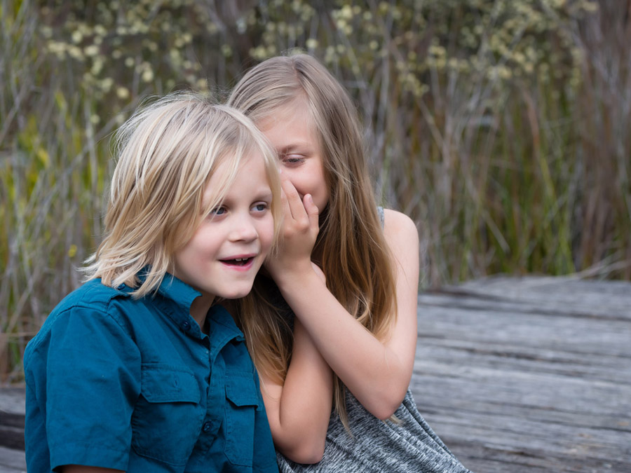 Girl whispering in boys ears in Sydney Millennium Parklands