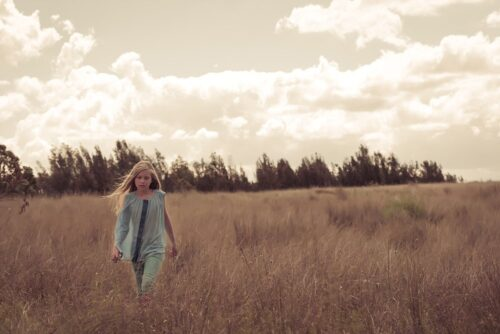 Girl walking in grassy fields yellow tone in Sydney Olympic Park