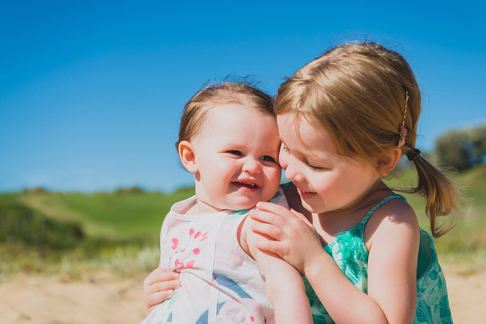 4 year old girl and baby sister playing in Little Bay Beach on a fine day with grassy hill in the background