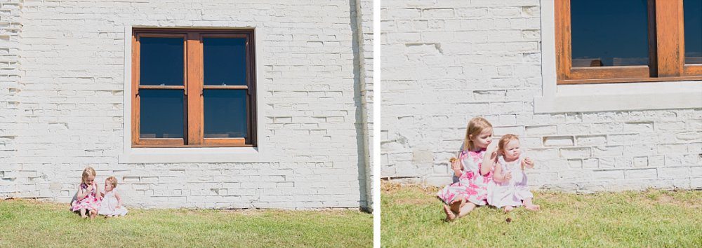 4 year old girl and baby sister in Little Bay sitting against white brick wall