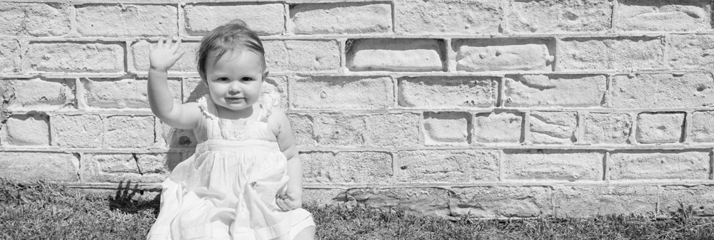 Baby girl in Little Bay sitting against white brick wall