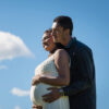 Pregnant Indian couple looking to left with clouds and blue sky in background