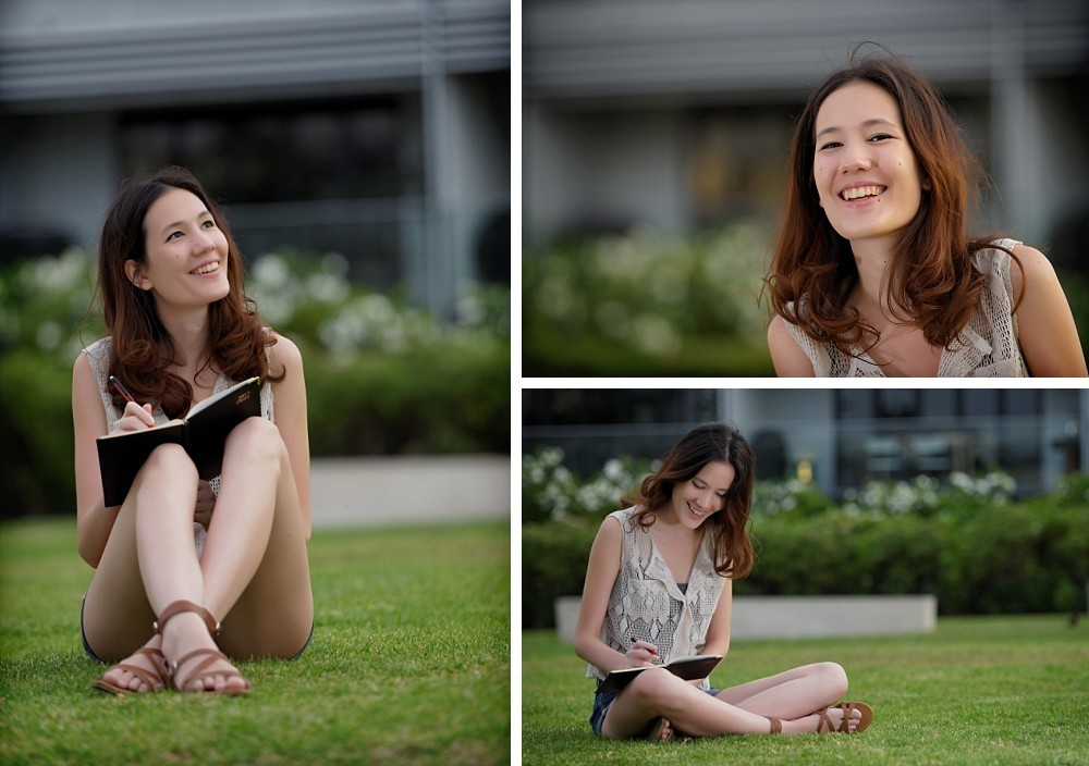 Young woman sitting on grass in Paddington with notebook