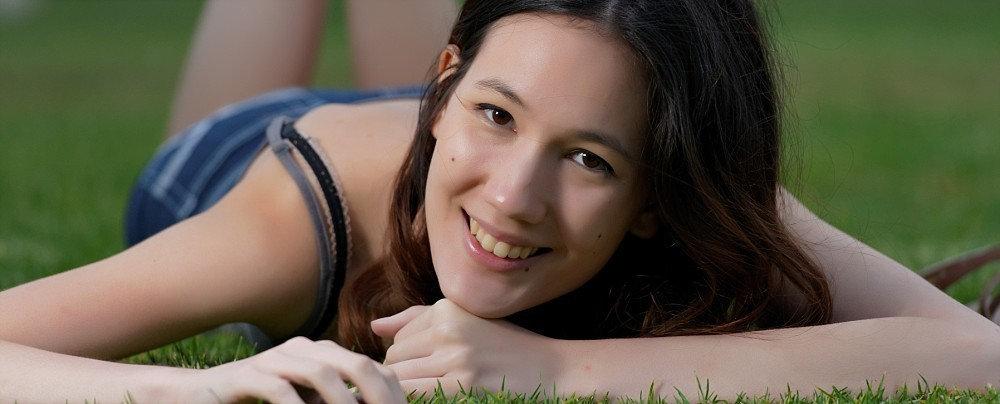 Young woman lying on grass smiling at camera
