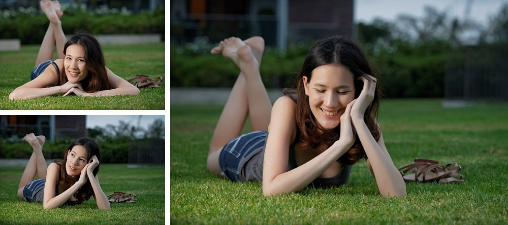 Young woman lying on grass feet up in air