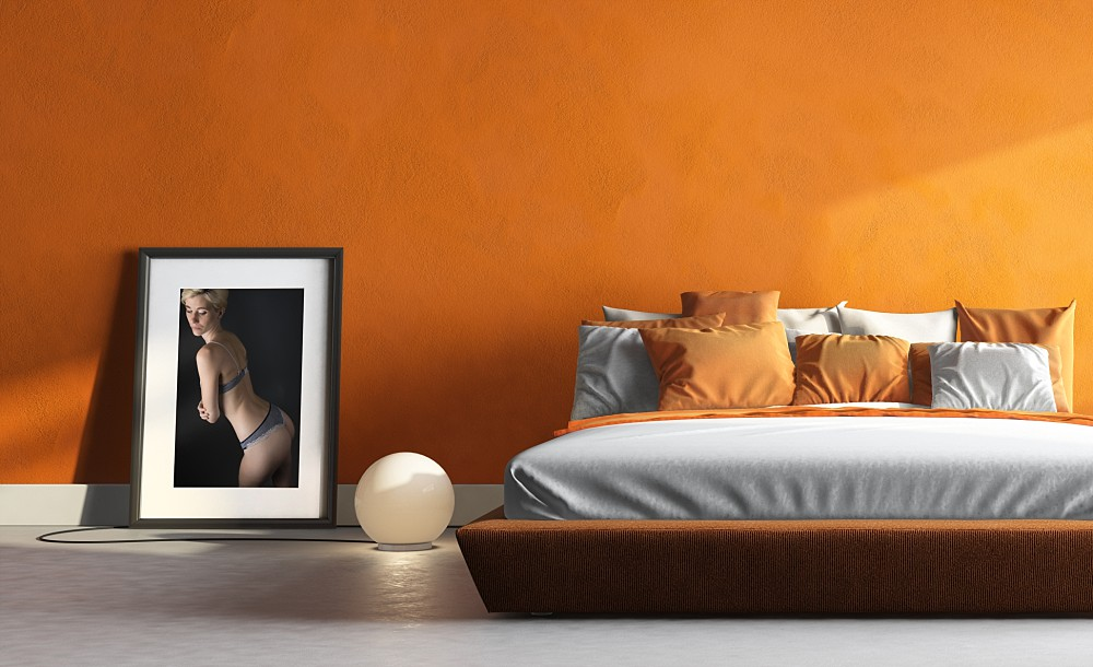 Framed boudoir photograph in an orange bedroom