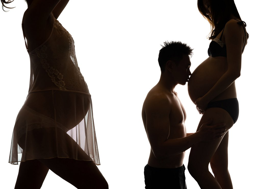 Pregnant Asian couple in sheer lace kissing belly in Sydney studio