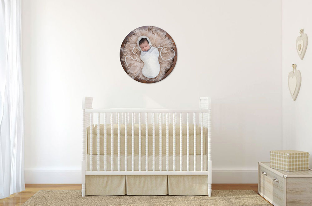 Circular metal artwork of wrap newborn baby in a bucket on wall in nursery above cot